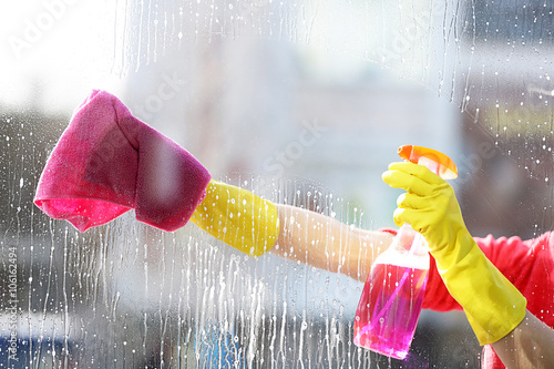 Fotografie, Obraz  Woman in a rubber glove cleaning window with sponge and detergent, close up