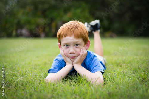 Fotografie, Obraz  Little boy with red hair lying in the grass while in deep thought