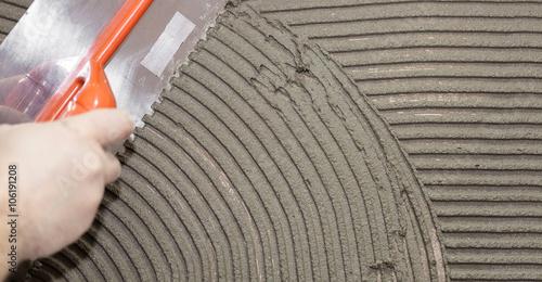 Obraz Worker tiler put cement - fototapety do salonu