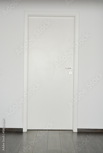 Fototapeta White closed door with silver doorknob on white wall background and parquet floor obraz na płótnie
