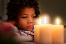 Sad Boy Looking At Candle.