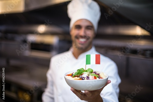 Foto  Handsome chef presenting meal with italian flag