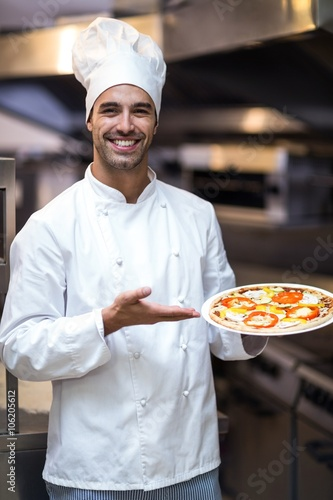 Handsome chef presenting pizza Wall mural