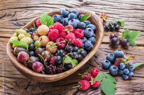 Fotografie, Obraz  Ripe berries in the wooden bowl.