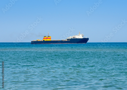 Spoed Foto op Canvas Eiland Cargo ship in the sea against the blue sky