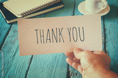 Photo man hand holding card with the word thank you. retro style image