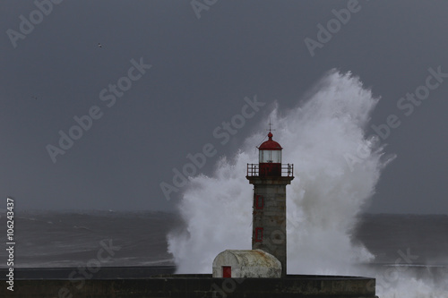 Poster Gris Storm with big waves near a lighthouse