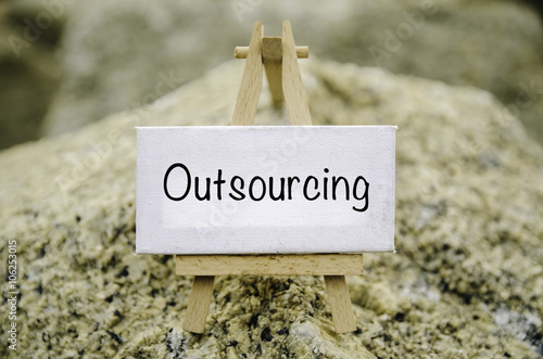 conceptual image, word OUTSOURCING on white canvas frame and wooden ...
