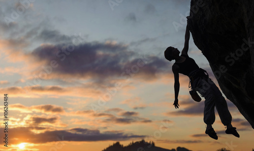 Fotografie, Obraz  Silhouette of athletic woman rock climber climbing steep rock wall against amazing sunset sky in the mountains on high altitude