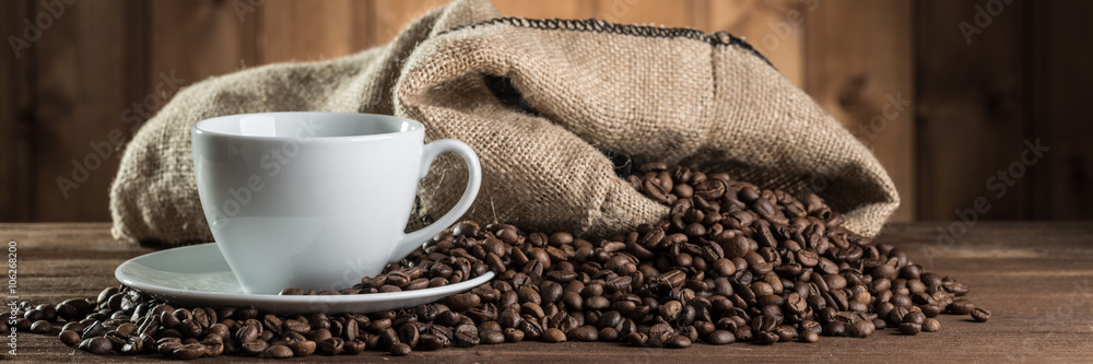 Fototapeta still life with coffee beans and cup on the wooden background
