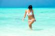 Красивая девушка в белом купальнике в прозрачной голубой воде тропического океана