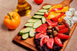 Rustic fresh Vegetables with Feta and olives on rustic wooden bo