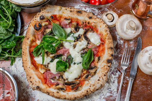 Pizza capricciosa with artichoke, ham and mushroom on wood backg