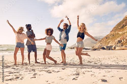 Plakat Szczęśliwi młodzi ludzie tanczy na plaży