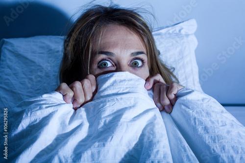 Fotomural  femme au lit cachée sous les draps apeurée