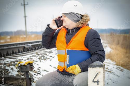 Fototapety, obrazy: Railway employee talking on smart phone near the signal relays