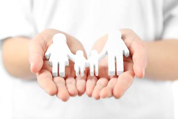 Fototapeta samoprzylepna Female hands holding family figure, close up
