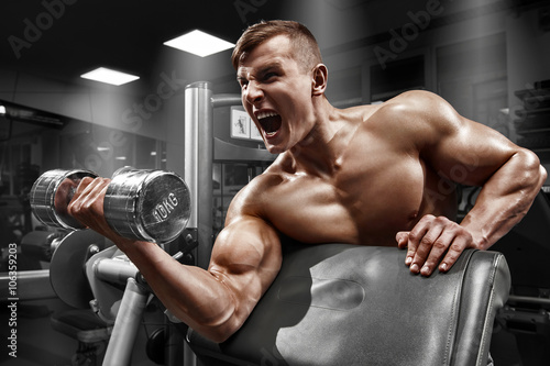 obraz dibond Muscular man working out in gym doing exercises with dumbbell at biceps, strong male naked torso abs