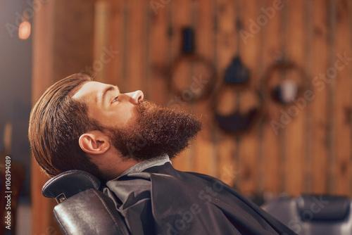 Pleasant man sitting in the barbershop