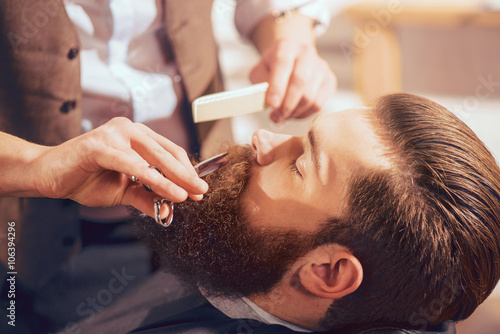Fotografie, Obraz  Professional barber cutting beard of handsome man