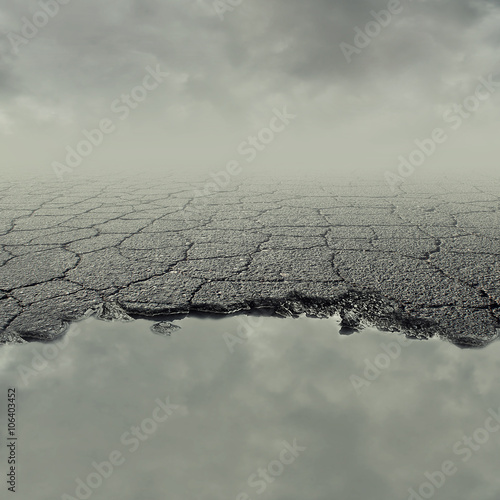 Carta da parati Pothole image of a broken cracked asphalt pavement with a dirty water puddle