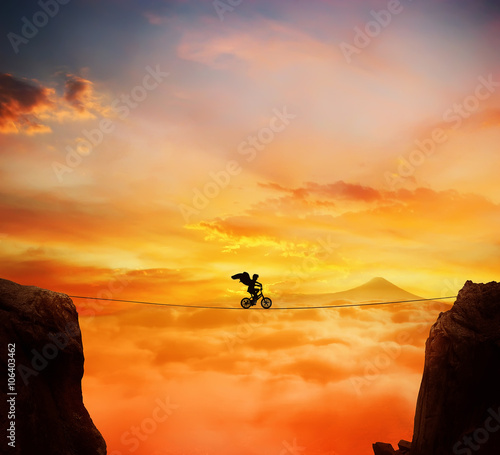 Canvastavla Boy with angel wings balance on a rope over a chasm riding a bicycle