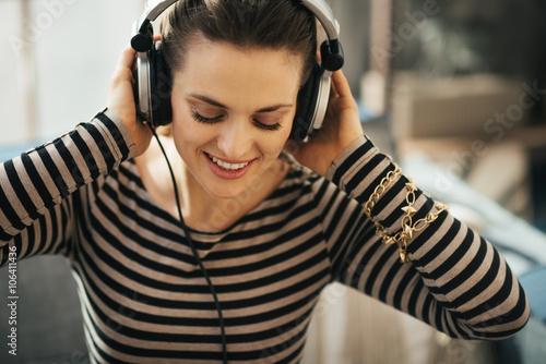 Foto  Frau, die Musik in der Dachbodenwohnung hört. Porträt schließen.