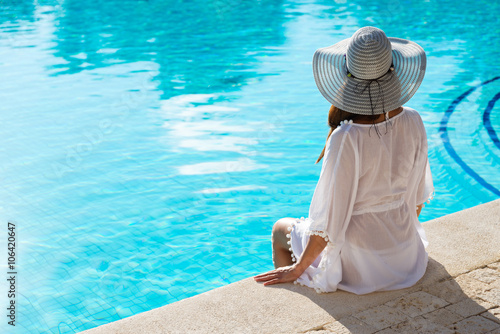 Obraz na płótnie Back view of fashion woman on summer vacation relaxing at luxury resort spa poolside