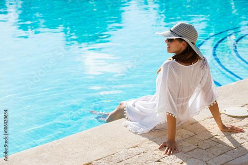 Plakat Fasonuje pięknej kobiety relaksuje przy luksusowym kurortu zdroju poolside na wakacje. Młoda modna dama jest ubranym słońce kapelusz i białego kaftan.