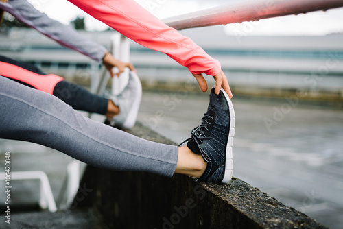 Fototapeta Two female athletes stretching legs and exercising
