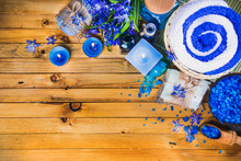 Spa Concept In Blue Tones On A Wooden Surface: Candle, Sea Salt, Flowers, Soaps, Essential Oils. Top View.