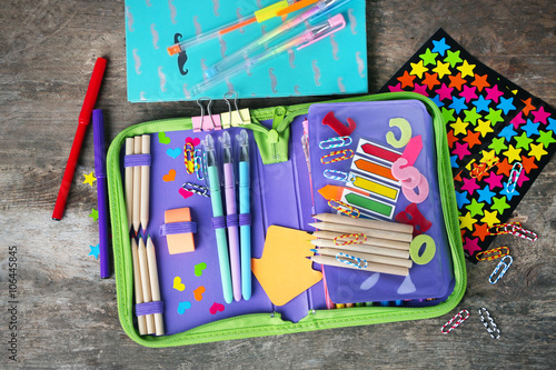 Photo Pencil case with various stationery on old  wooden table