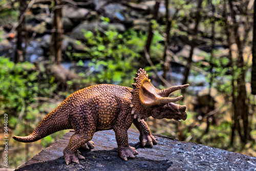 Photo  Brown Triceratops dinosaur  with woods in the background