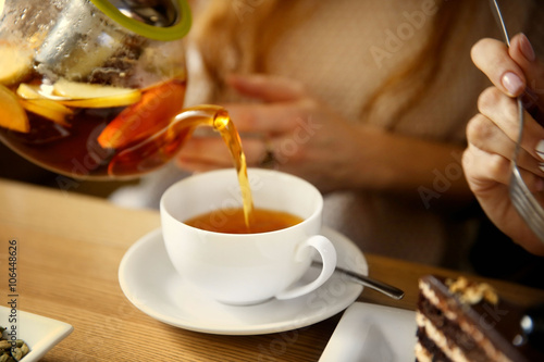 Pouring tea into a white cup in cafe or restaurant