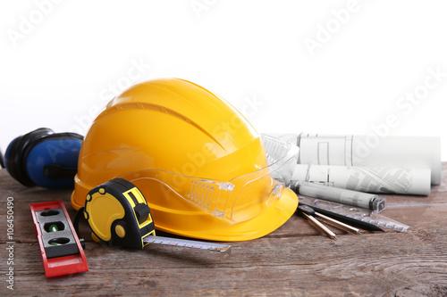 Fototapeta Yellow helmet and blueprint on a white background. obraz na płótnie