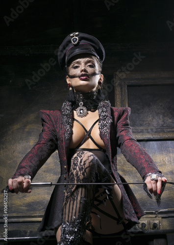 Photo  Very beautiful woman in a cap, with a whip