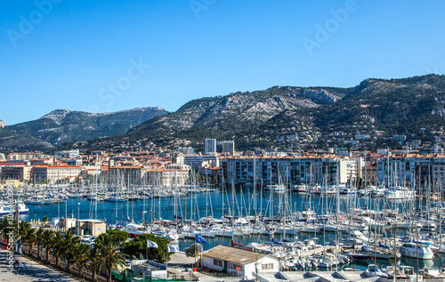 Toulon, France, the harbor crowded of boats with the city in the background.