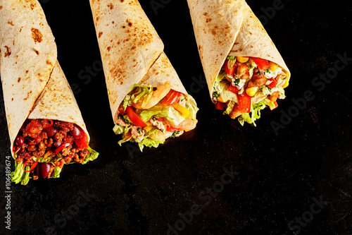 Fotografía  Trio of Tex Mex Fajita Wraps on Black Background