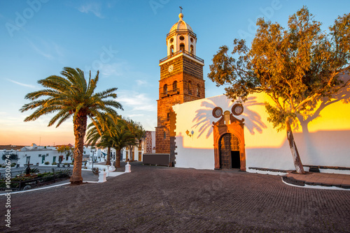 Tuinposter Canarische Eilanden Central square with old church Nuestra Senora de Guadalupe in Teguise village on the sunset on lanzarote island