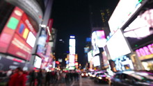 Times Square, New York City, Manhattan Background Out Of Focus With Blurry Unfocused City Lights And Billboards. City At Night With Cars And Pedestrians People Walking.