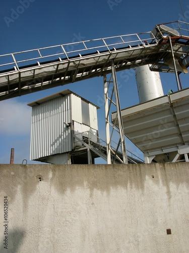 Photo Modernes Kieswerk mit Trichter und Förderband hinter einer grauen Betonmauer in