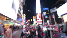 People At Times Square, New York City Background At The Red Chair. Out Of Focus City Lights, People Walking And Billboards At Night Defocused Blurry. Manhattan City Life Backgrounds.