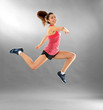 Young sporty woman running on grey background