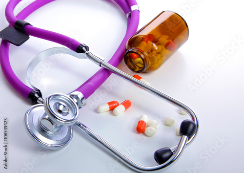 Fotografering  Pills ,tablets and stethoscope on white background