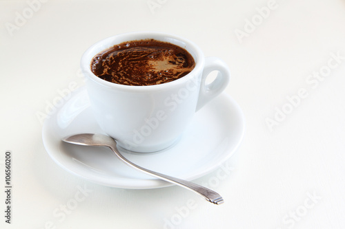 Fotobehang Chocolade cup of coffee and silver spoon/cup of coffee and silver spoon on a white table