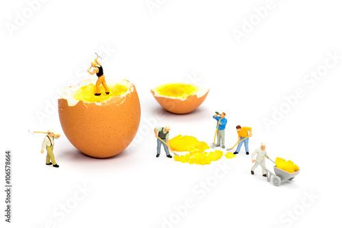 Fotografie, Obraz  Team of miniature human figurines transporting chicken egg yolk