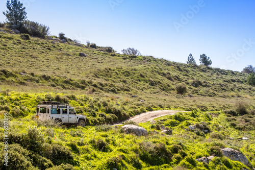 Photo  SUV rides on the country road among hills and meadows, Israel