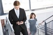 Businesspeople climbing staircase in office