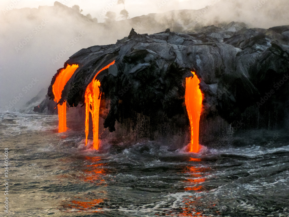 Fototapeta Sea view of Kilauea Volcano in Big Island, Hawaii, United States. A restless volcano that has been in business since 1983. Shot taken at sunset when the lava glows in the dark as jumps into the sea.