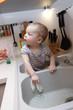Baby boy sitting in the kitchen sink